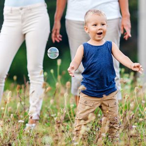 Happy child with family having a great time blowing bubbles outdoors
