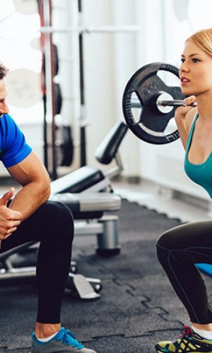 Young sporty woman is  lifting barbell with assistance and motivation of her personal trainer at the gym.